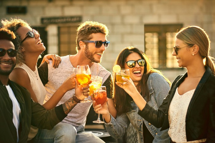 Group of five friends having drinks and smiling outside.