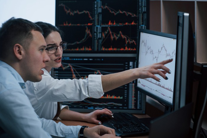 Two persons appearing confused while studying stock price charts on computer screens.