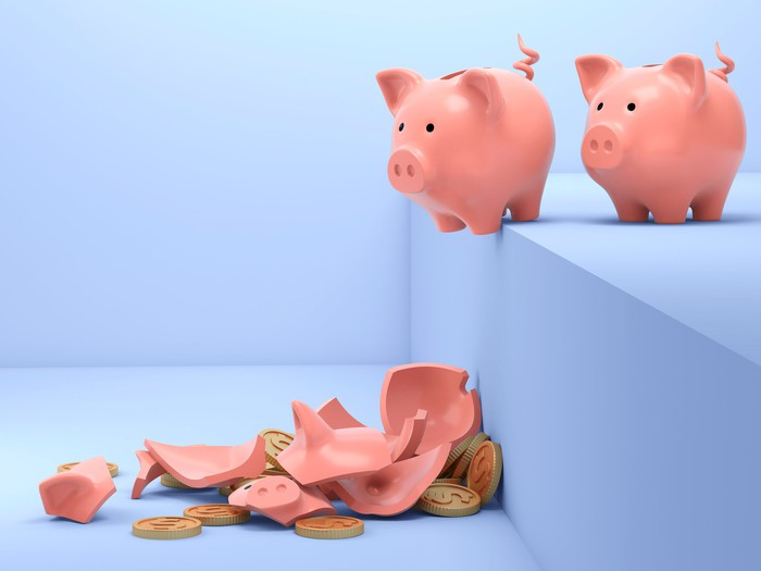Piggy banks lining up to fall off a step.