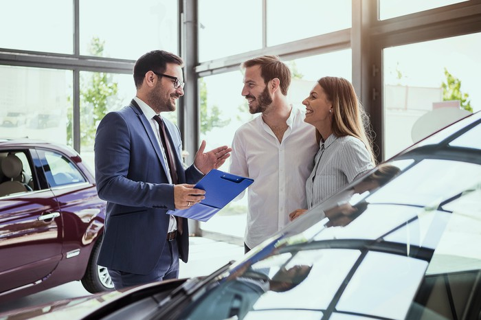 A young couple purchasing a car off a salesperson, looking extremely happy