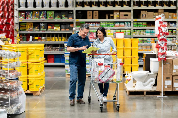 Two people look at a piece of paper while one pushes a wagon in a warehouse store.