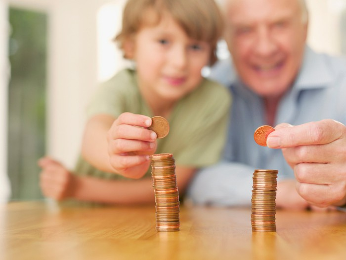 A child and grandparent each make a stack of coins on a table.