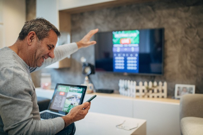 A man playing a digital sports betting game with his sportphone.