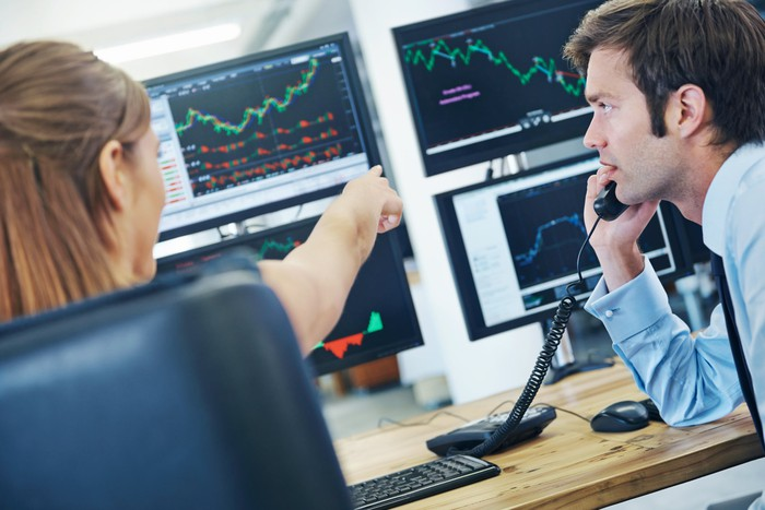 Two persons studying stock price charts on computer screens.