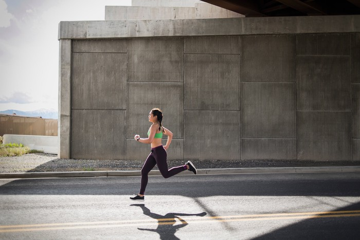 A person in workout gear running on a street.