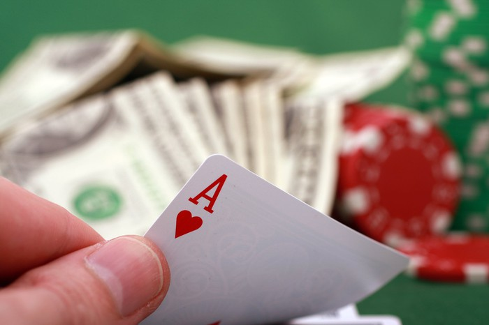 Fingers holding an ace of hearts card, with cash and poker chips in the background.
