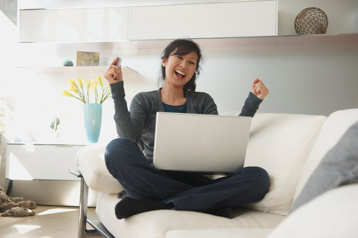 A person sitting on a couch with a laptop, extremely happy about an online purchase