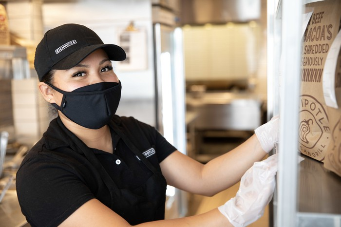 A chipotle worker wearing baseball cap and a COVID-19 mask reaches for a bag of chips in a restaurant