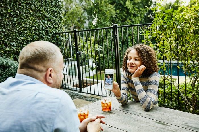 Famille partageant une photo à une table en plein air.