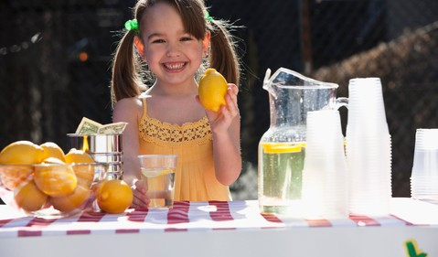 A girl holding a lemon and standing in front of a table ith lemonade and cups