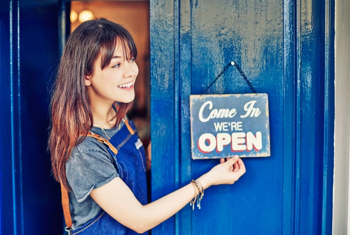 A smiling business owner hangs an open sign on his blue shop door