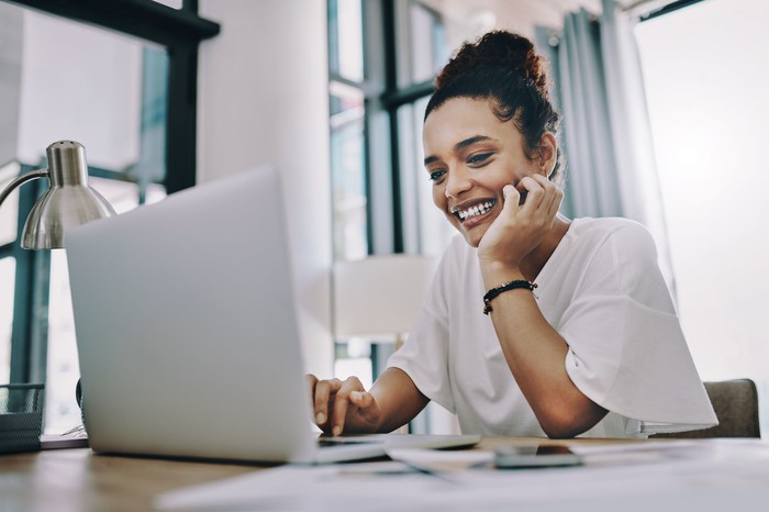 Smiling person with hand on chin looking at laptop