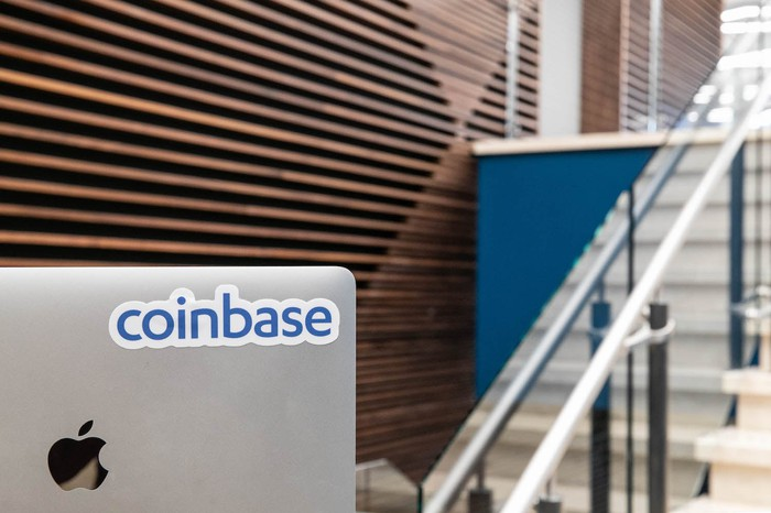 The Coinbase logo is displayed on a computer in an office setting.