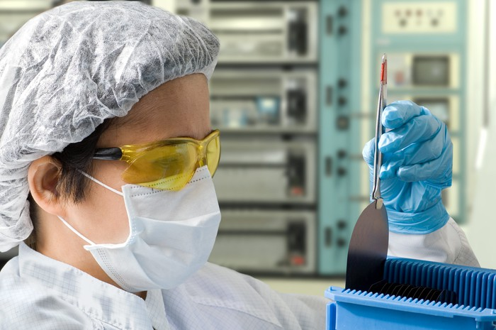 A technician inspects a silicone wafer in a sterile environment.