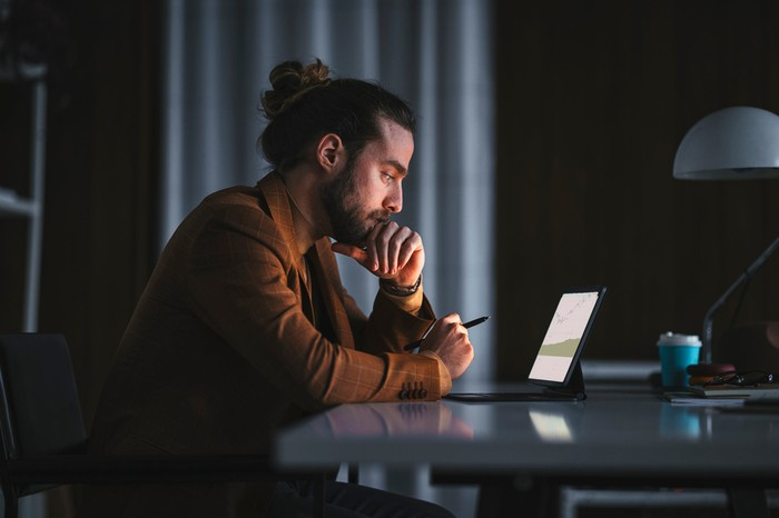 A person sits in a dark room looking at a computer, seemingly deep in thought.