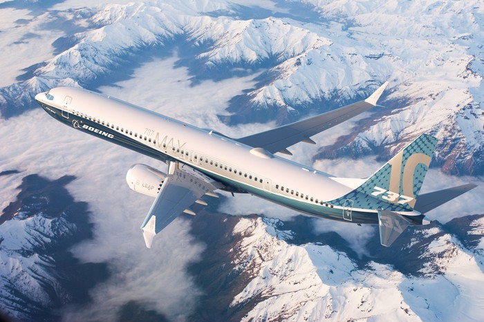 A Boeing 737 MAX 10 flying over snow-capped mountains.