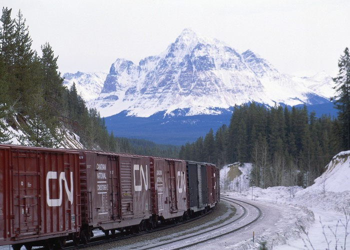 A Canadian National train goes through a mountain pass.