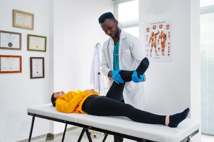 A chiropractor treats a patient's injured knee.