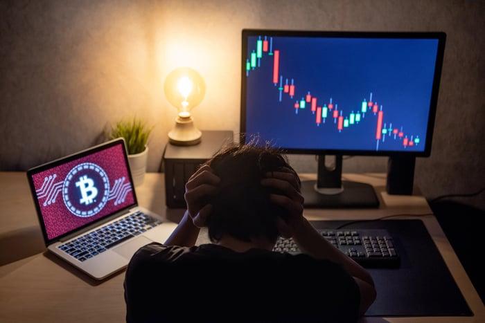 Trader en détresse au bureau avec graphique boursier en baisse sur un écran et logo bitcoin sur l'autre.