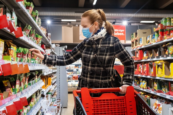 A shopper wearing a mask pushes their cart while taking an item off the shelf