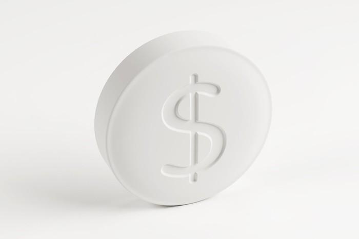A white generic drug pill with a dollar sign stamped into it.
