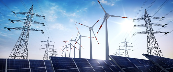 power transmission towers with solar panels and wind turbines.