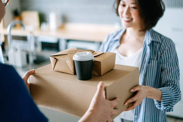 Smiling woman receives food delivery  in brown boxes.