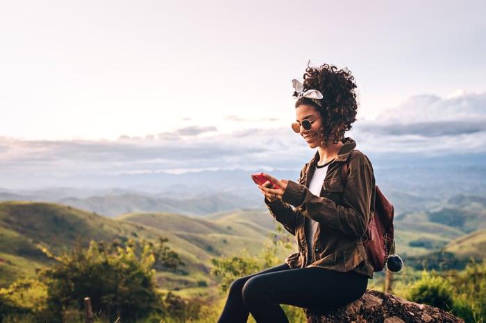 Le randonneur est assis sur un rocher et accède au service téléphonique depuis le sommet d'une montagne.