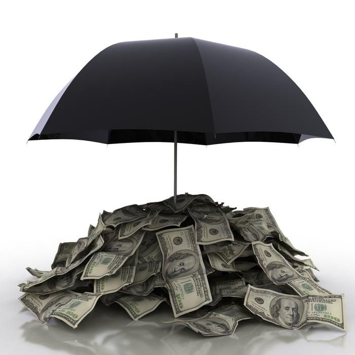 Black umbrella covering dollar bills