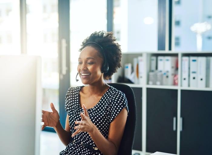 Une femme portant un casque et parlant à un client à son bureau.