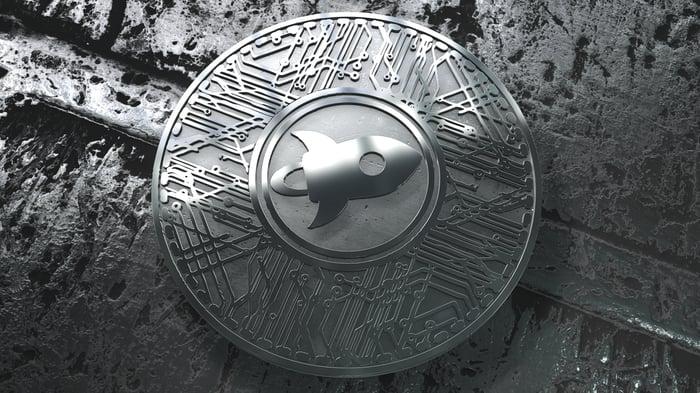 A silver Stellar Lumen coin with a rocket ship logo.