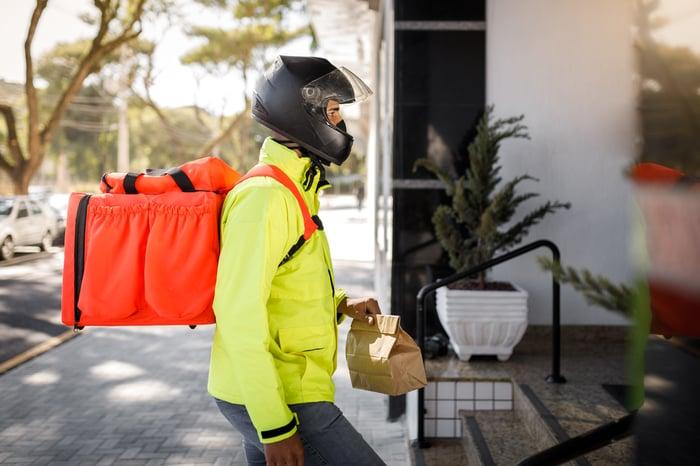 Un chauffeur-livreur vêtu d'une veste jaune vif livre de la nourriture.