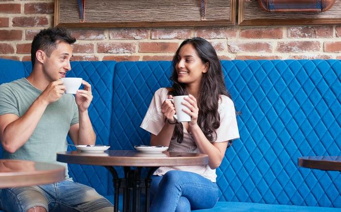 Deux personnes buvant des boissons dans un café.