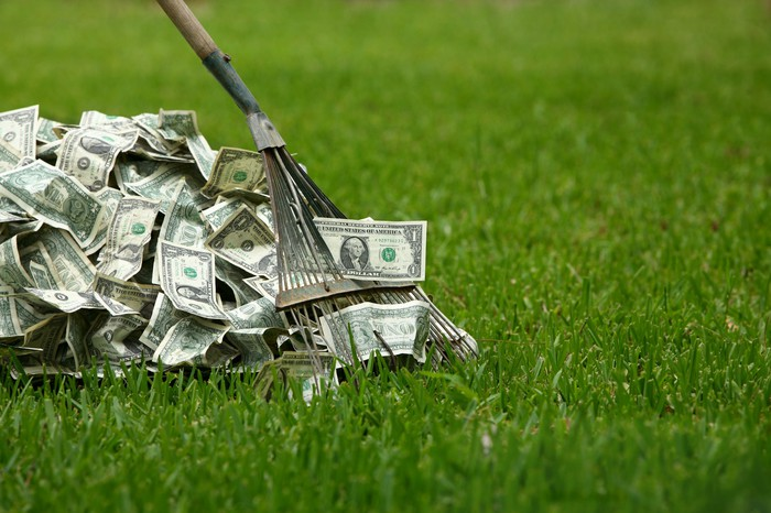 A rake drags a pile of U.S. $1 bills through a lawn of grass.