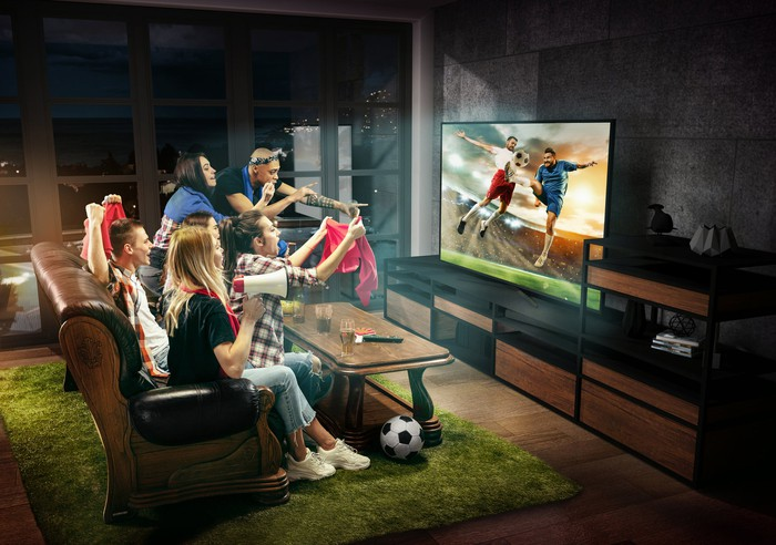Sports fans in a living room with a turf rug gather to watch a soccer match.