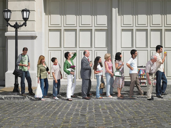 Une longue file de personnes debout à l'extérieur sur une route pavée en attente.