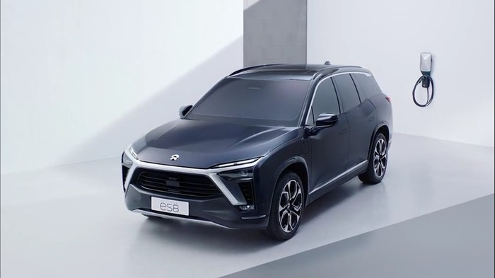Dark blue Nio ES8 electric SUV in front of wall battery charger.