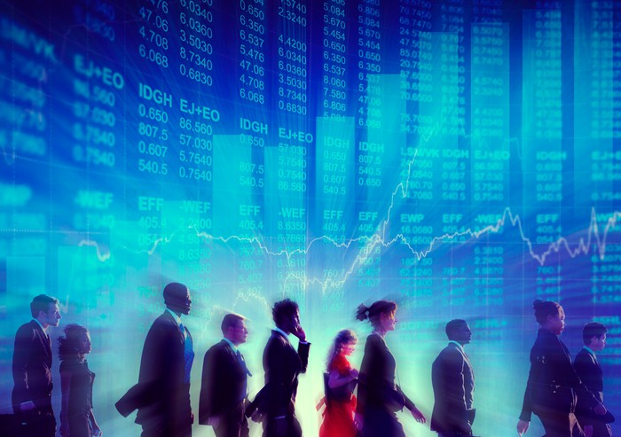group of investors walking in front of wall with stocks and bar charts going higher.