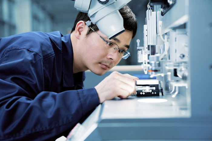 A worker examines a medical device to perform a quality control check.