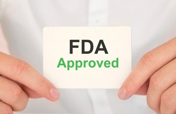 """Two hands holding a card with """"FDA approved"""" printed on it."""