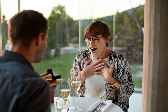Man giving his surprised girlfriend an engagement ring.