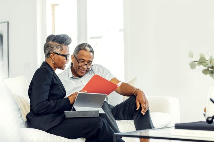 Deux personnes avec un ordinateur portable discutent de papiers.