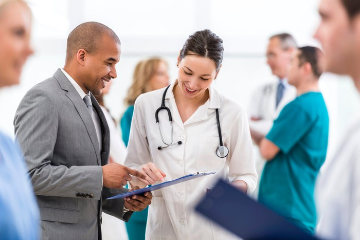 A medical professional looking at a tablet with another person.