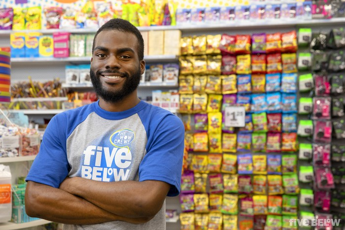 An employee of Five Below smiles with arms crossed in a store location.
