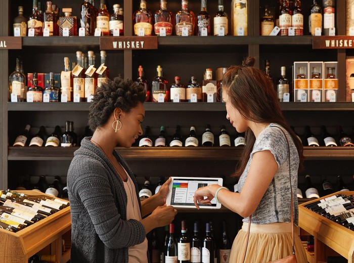 Two people in a liquor store pointing at a Square point-of-sale tablet.
