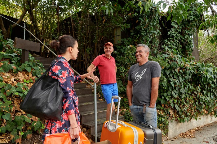 Three people standing in a garden with suitcases.