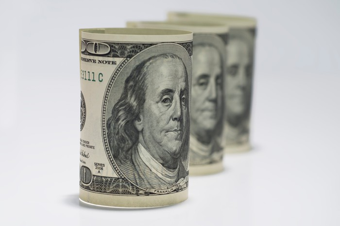 Trois billets de cent dollars enroulés alignés dans une rangée ordonnée.