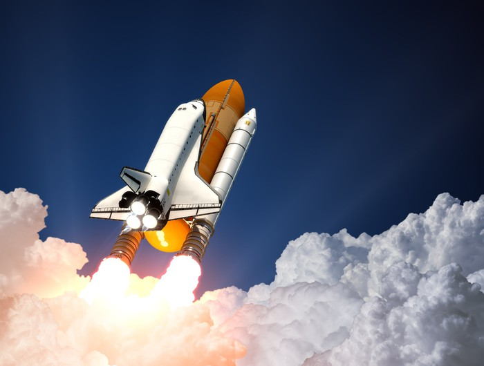 Rockets pushing a space shuttle up through clouds.