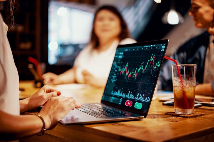Les gens sont assis autour d'une table et discutent pendant que l'un d'eux utilise un ordinateur portable avec des informations financières à l'écran.