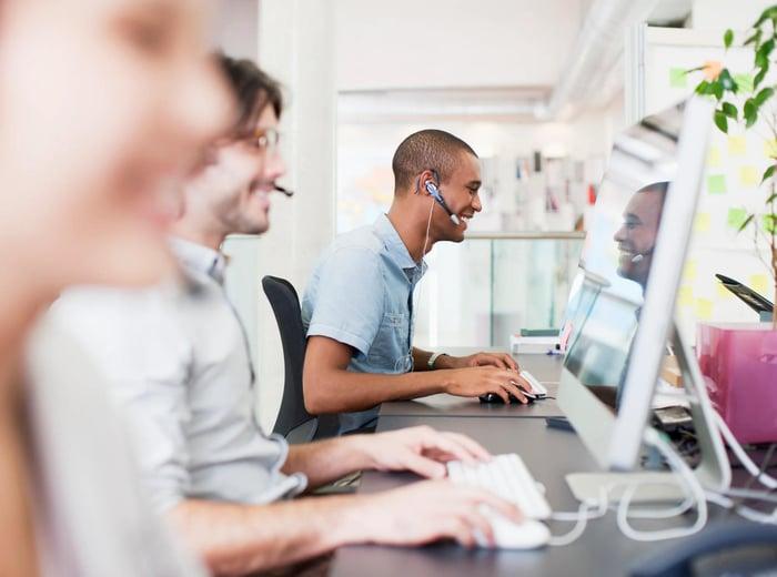 Trois personnes assises à un bureau avec des casques regardant des écrans d'ordinateur.